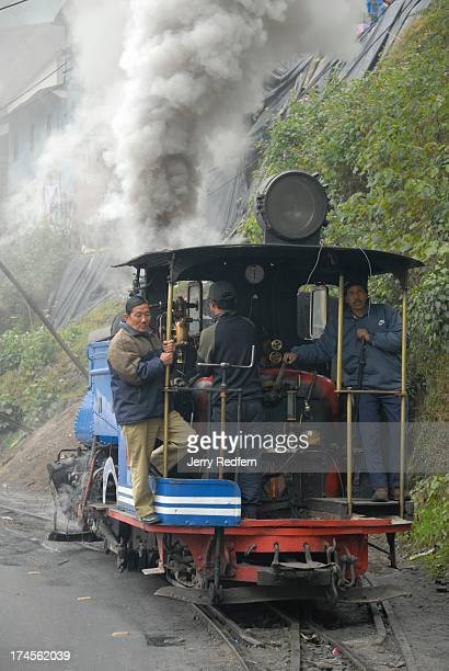 A locomotive crew slowly backs a historic coalfired steam engine from the engine barn in Darjeeling before hooking it up to passenger cars for the...