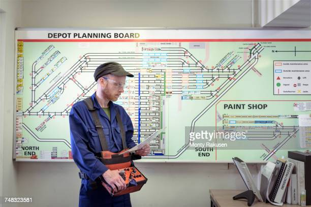 Locomotive engineer with engine shed plans in train works