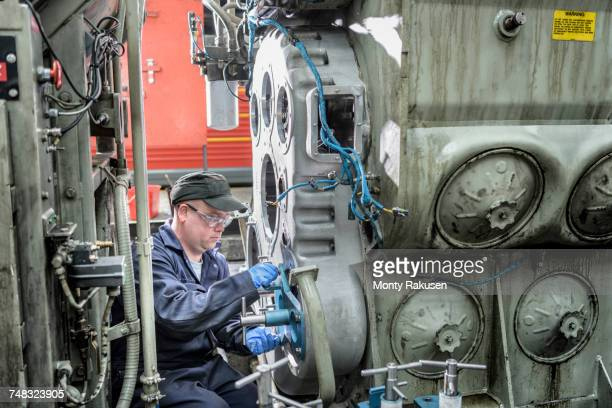 Locomotive engineer working on locomotive in train works