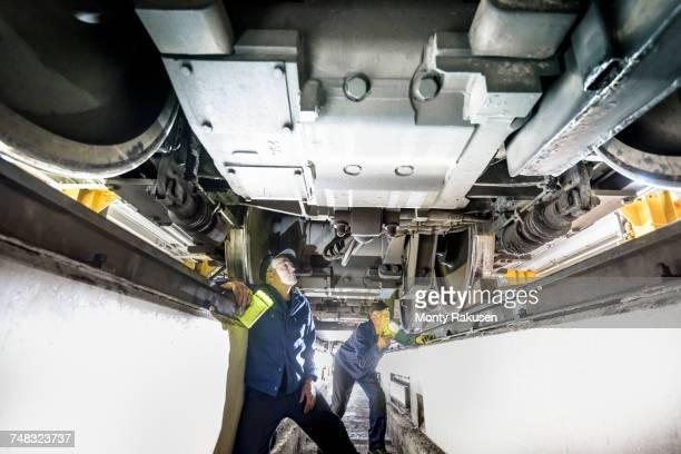 Locomotive engineers inspecting underside of locomotive in train works