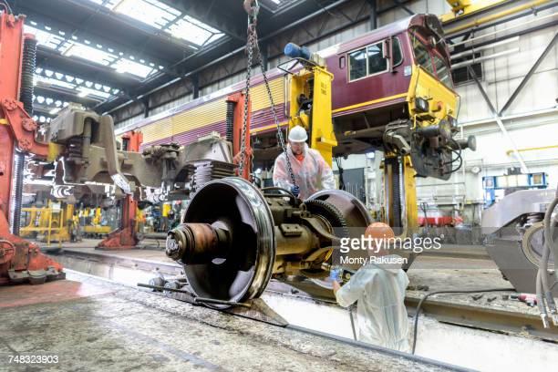 Locomotive engineers working on locomotive in train works