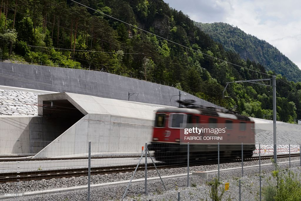 A locomotive makes its way next to one of the tube at the north entrance of the new Gotthard Base Tunnel the world's longest train tunnel on the eve of its opening ceremony on May 31, 2016 in Erstfeld. The new Gotthard Base Tunnel (GBT) is set to become the world's longest railway tunnel when it opens on June 1. The 57-kilometre (35.4-mile) tunnel, which runs under the Alps, was first conceived in sketch-form in 1947 but construction began 17 years ago. / AFP / FABRICE