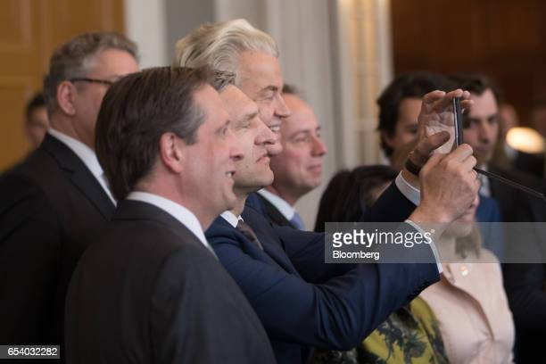 Lodewijk Asscher leader of the Labour party center takes a selfie photograph with Geert Wilders leader of the Dutch Freedom Party right and Alexander...