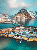 Aerial view of Lofoten winter scenery with traditional fisherman Rorbuer cabins and mountain peaks at sunrise, Sakrisoy, village of Reine, Norway