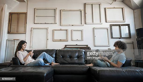 Loft decor. A wall hung with pictures in frames, reversed to show the backs. A young couple sitting on the sofa, one using a smart phone and one holding a digital tablet.
