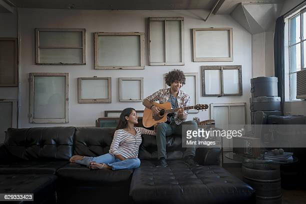 Loft decor. A wall hung with pictures in frames, reversed to show the backs. A man playing a guitar and a woman sitting on a sofa.