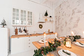 Loft style Apartment, large spacious living room with dining table and kitchen. Room with Christmas tree. Light white brick wall