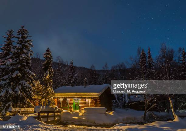 Cozy and inviting log cabin with icicles in winter, snow, pine trees, starry sky
