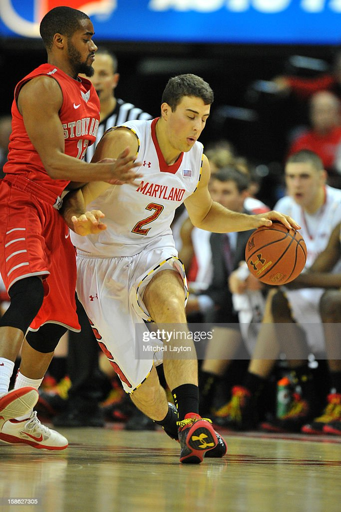 Logan Aronhalt #2 of the Maryland Terrapins dribbles by Marcus Rouse #12 of Stony Brook Seawolves during a college basketball game on December 21, 2012 at the Comcast Center in College Park, Maryland.