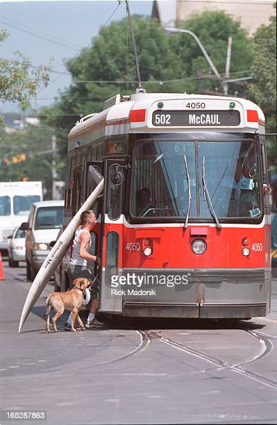 Logan Black of Toronto and his dog Rocky prepare to board an eastend streetcar as they make there way to the waterfront Black uses an old windsurfing...