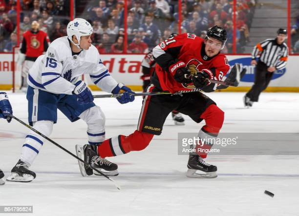 Logan Brown of the Ottawa Senators shoots the puck into the offensive zone against pressure from Matt Martin of the Toronto Maple Leafs at Canadian...