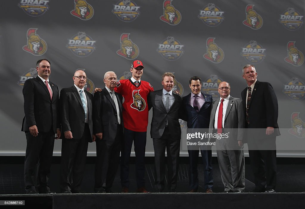 Logan Brown, selected 11th overall by the Ottawa Senators, poses onstage with the Senators team personnel during round one of the 2016 NHL Draft at First Niagara Center on June 24, 2016 in Buffalo, New York.