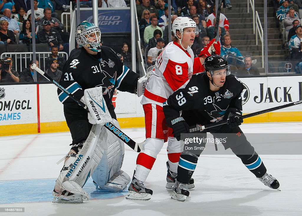 Logan Couture #39 and Antti Niemi #31 of the San Jose Sharks defend against Justin Abdelkader #8 of the Detroit Red Wings during an NHL game on March 28, 2013 at HP Pavilion in San Jose, California.