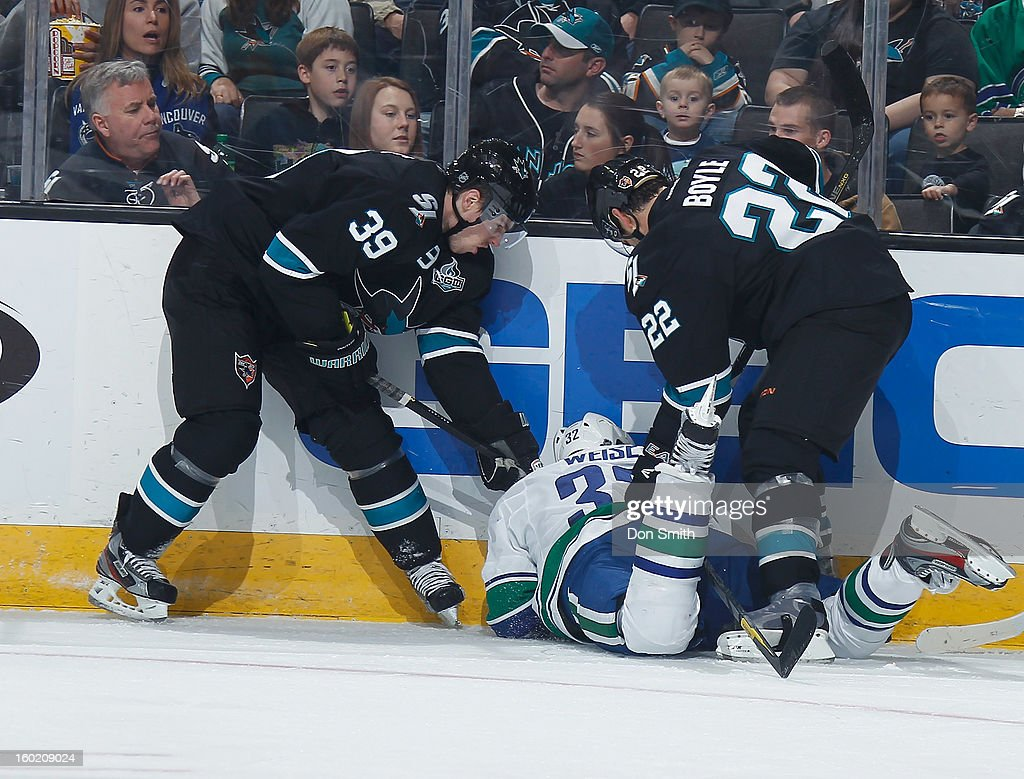 Logan Couture #39 and Dan Boyle #22 of the San Jose Sharks fight for the puck against Dale Weise #32 of the Vancouver Canucks during an NHL game on January 27, 2013 at HP Pavilion in San Jose, California.