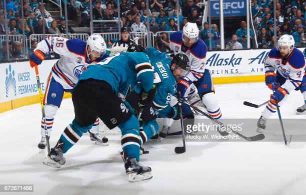 Logan Couture and Joonas Donskoi of the San Jose Sharks battle for the puck against Drake Caggiula and Andrej Sekera of the Edmonton Oilers in Game...