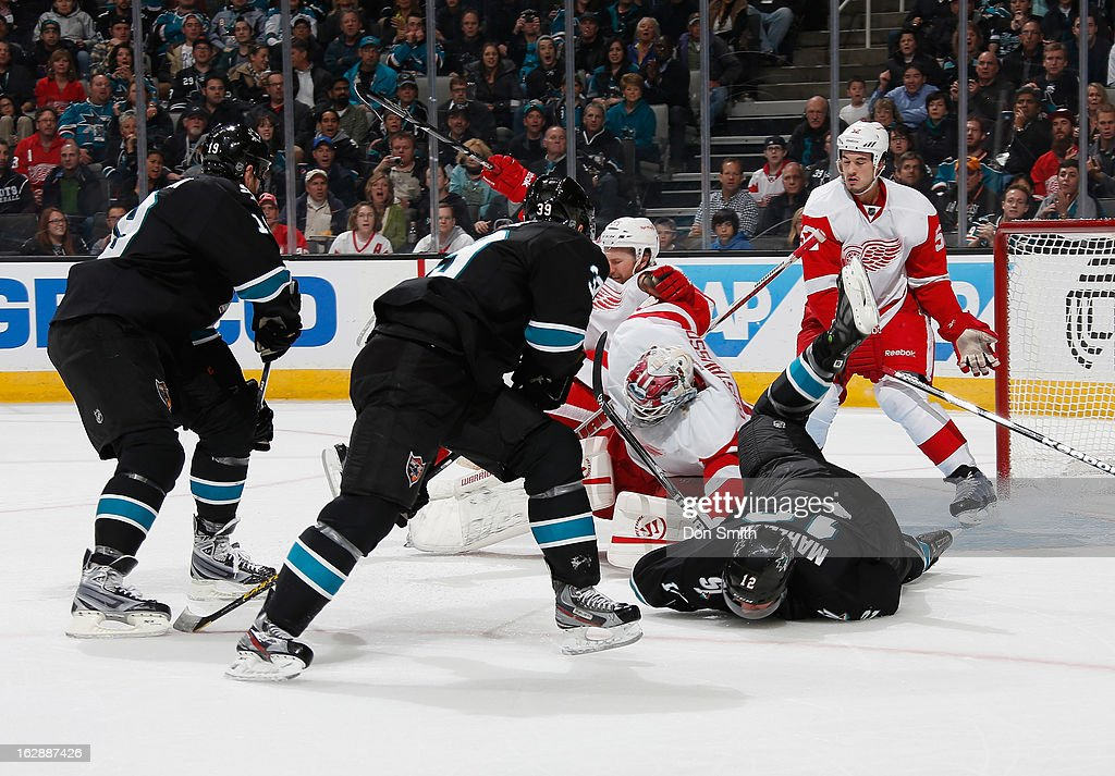 Logan Couture #39, Joe Thornton #19 and Patrick Marleau #12 of the San Jose Sharks crash the net against Jonas Gustavsson #50 and Jonathan Ericsson #52 of the Detroit Red Wings during an NHL game on February 28, 2013 at HP Pavilion in San Jose, California.
