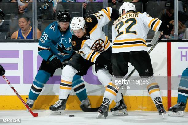 Logan Couture of the San Jose Sharks along with Charlie McAvoy and Peter Cehlarik of the Boston Bruins battle for the puck at SAP Center on November...