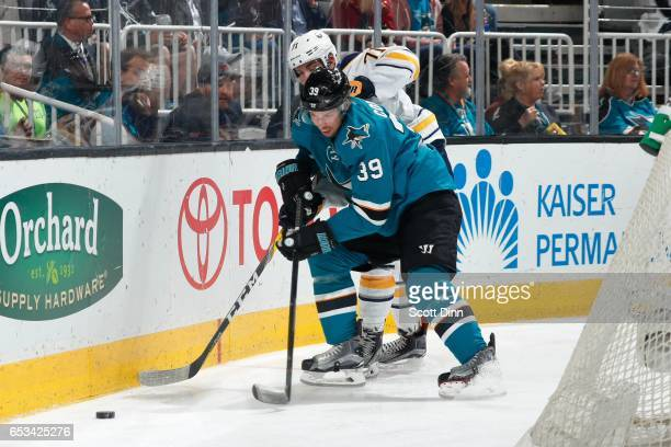 Logan Couture of the San Jose Sharks and Evan Rodrigues of the Buffalo Sabres battle for the puck at SAP Center at San Jose on March 14 2017 in San...
