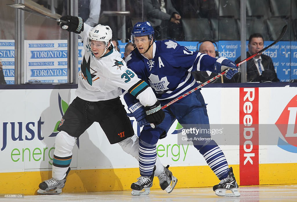 <a gi-track='captionPersonalityLinkClicked' href=/galleries/search?phrase=Logan+Couture&family=editorial&specificpeople=809700 ng-click='$event.stopPropagation()'>Logan Couture</a> #39 of the San Jose Sharks battles against <a gi-track='captionPersonalityLinkClicked' href=/galleries/search?phrase=Jay+McClement&family=editorial&specificpeople=575233 ng-click='$event.stopPropagation()'>Jay McClement</a> #11 of the Toronto Maple Leafs during an NHL game at the Air Canada Centre on December 3, 2013 in Toronto, Ontario, Canada. The Sharks defeated the Leafs 4-2.