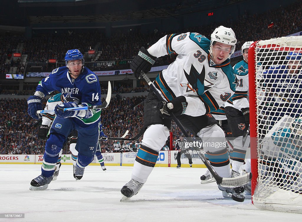<a gi-track='captionPersonalityLinkClicked' href=/galleries/search?phrase=Logan+Couture&family=editorial&specificpeople=809700 ng-click='$event.stopPropagation()'>Logan Couture</a> #39 of the San Jose Sharks clears the puck while <a gi-track='captionPersonalityLinkClicked' href=/galleries/search?phrase=Alexandre+Burrows&family=editorial&specificpeople=592489 ng-click='$event.stopPropagation()'>Alexandre Burrows</a> #14 of the Vancouver Canucks moves in during Game One of the Western Conference Quarterfinals during the 2013 NHL Stanley Cup Playoffs at Rogers Arena on May 1, 2013 in Vancouver, British Columbia, Canada. San Jose won 3-1.