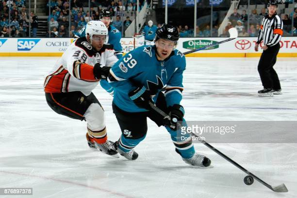 Logan Couture of the San Jose Sharks controls the puck ahead of Derek Grant of the Anaheim Ducks at SAP Center on November 20 2017 in San Jose...