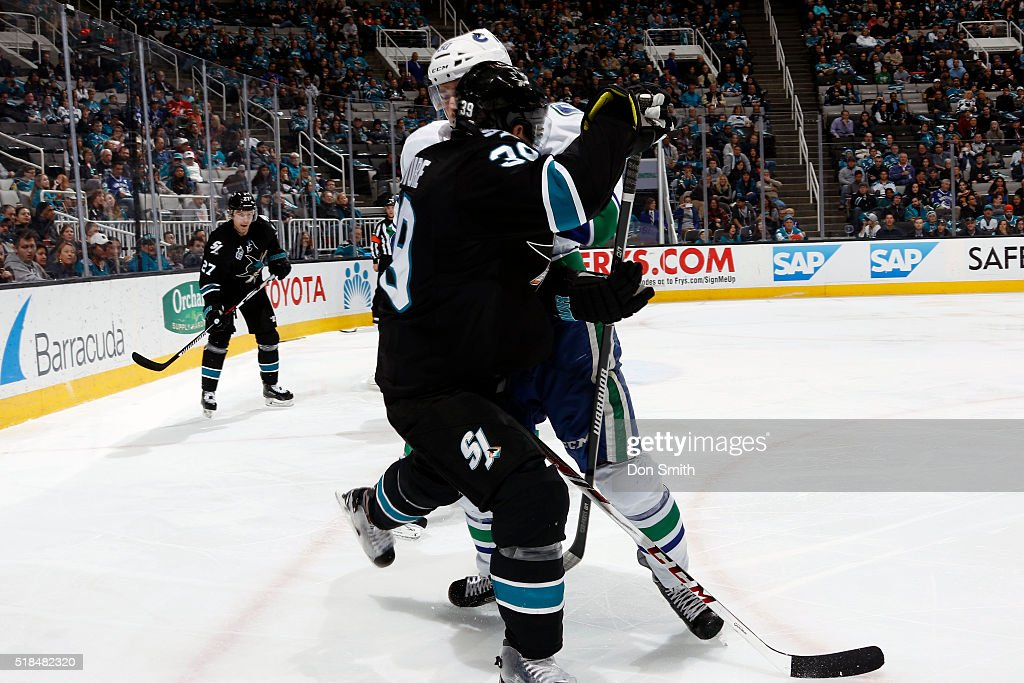 Logan Couture #39 of the San Jose Sharks gets stuffed by Brendan Gaunce #50 of the Vancouver Canucks during a NHL game at the SAP Center at San Jose on March 31, 2016 in San Jose, California.