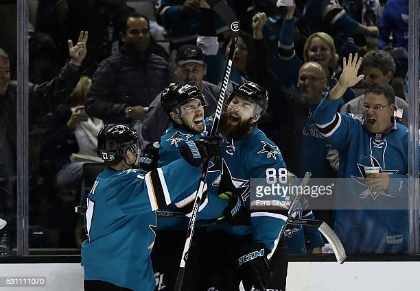 Logan Couture of the San Jose Sharks is congratulated by Brent Burns and Joonas Donskoi after Couture scored in the second period against the...