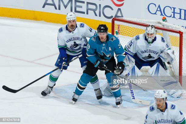 Logan Couture of the San Jose Sharks is defended by Erik Gudbranson and Jacob Markstrom of the Vancouver Canucks at SAP Center on November 11 2017 in...