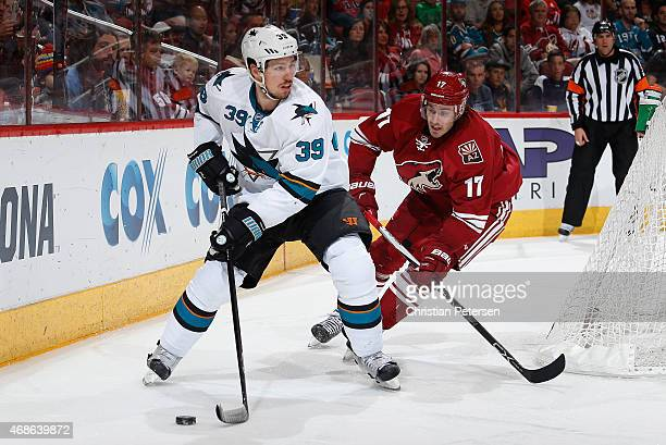 Logan Couture of the San Jose Sharks looks to center the puck under pressure from John Moore of the Arizona Coyotes during the third period of the...