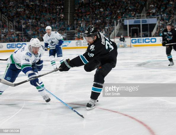 Logan Couture of the San Jose Sharks scores a goal against Alexandre Burrows of the Vancouver Canucks in Game One of the Western Conference...
