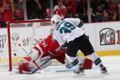 Logan Couture of the San Jose Sharks scores the game winning goal in a shootout on Jimmy Howard of the Detroit Red Wings during an NHL game at Joe...