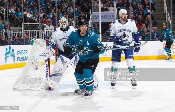 Logan Couture of the San Jose Sharks skates against Jacob Markstrom and Erik Gudbranson of the Vancouver Canucks at SAP Center on November 11 2017 in...