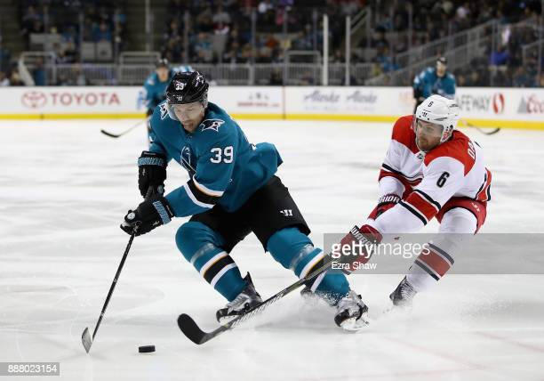 Logan Couture of the San Jose Sharks tries to keep puck away from Klas Dahlbeck of the Carolina Hurricanes at SAP Center on December 7 2017 in San...
