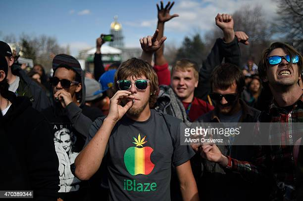 Logan Cressler smokes a marijuana cigarette as he and other fans listen to the rapper Rick Ross perform during Denver's annual 4/20 festival at Civic...