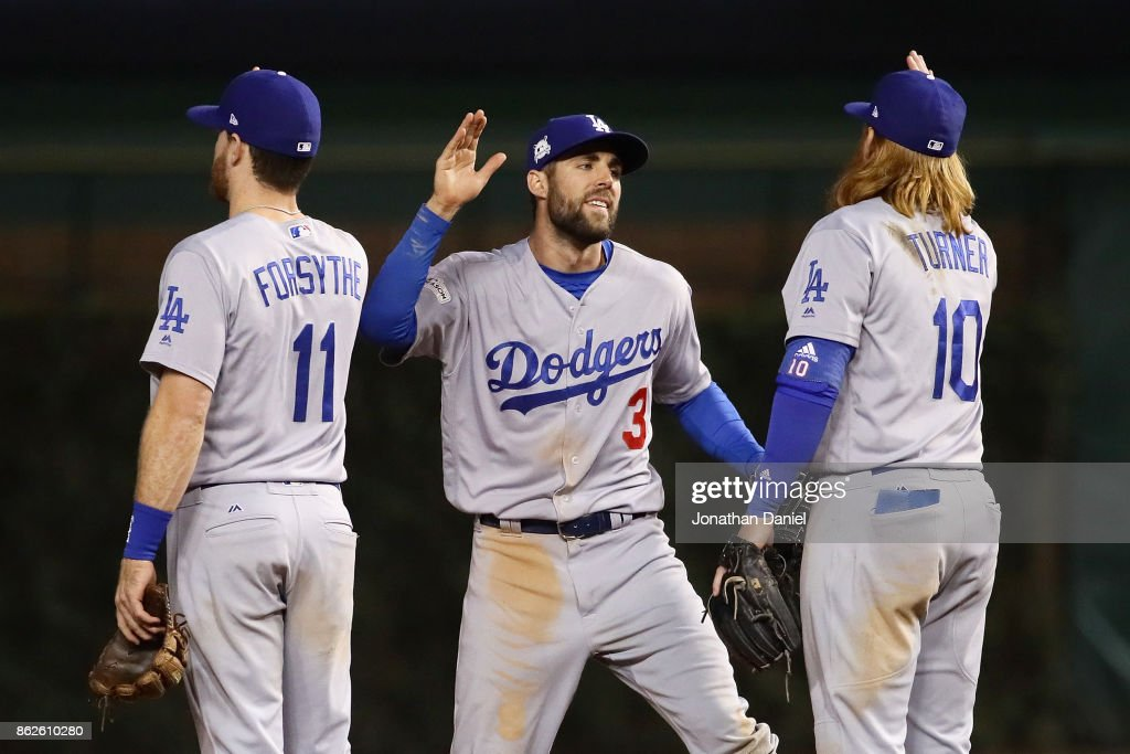 Logan Forsythe #11, Chris Taylor #3, and Justin Turner #10 of the Los Angeles Dodgers celebrate after beating the Chicago Cubs 6-1 during game three of the National League Championship Series at Wrigley Field on October 17, 2017 in Chicago, Illinois.