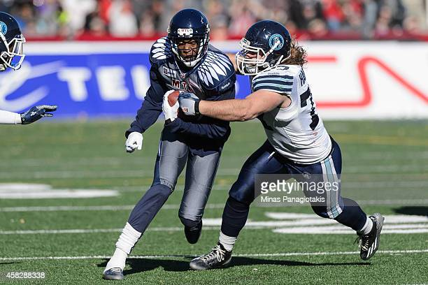 Logan Harrell of the Toronto Argonauts tackles Duron Carter of the Montreal Alouettes during the CFL game at Percival Molson Stadium on November 2...