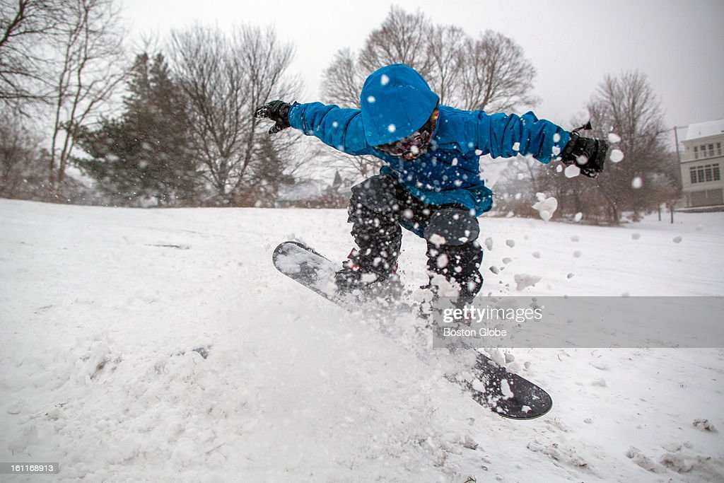 Logan Kolesha, 7, snowboards over a handmade jump on March's HIll as a winter storm, expected to dump as much as 24 inches of snow in the region, intensified in Newburyport.