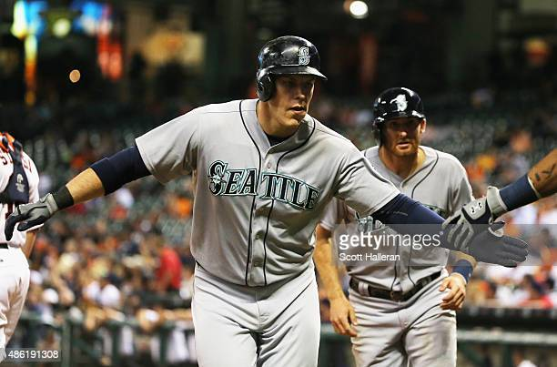 Logan Morrison and Brad Miller of the Seattle Mariners come in to score after Morrison hit a tworun home run in the eighth inning of their game...