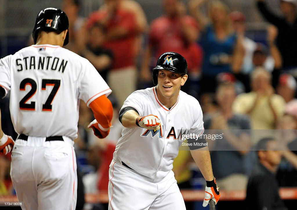 Logan Morrison #5 of the Miami Marlins greets teammate Giancarlo Stanton #27 of the Miami Marlins after Stanton hit a solo home run in the ninth inning against the Washington Nationals at Marlins Park on July 13, 2013 in Miami, Florida.