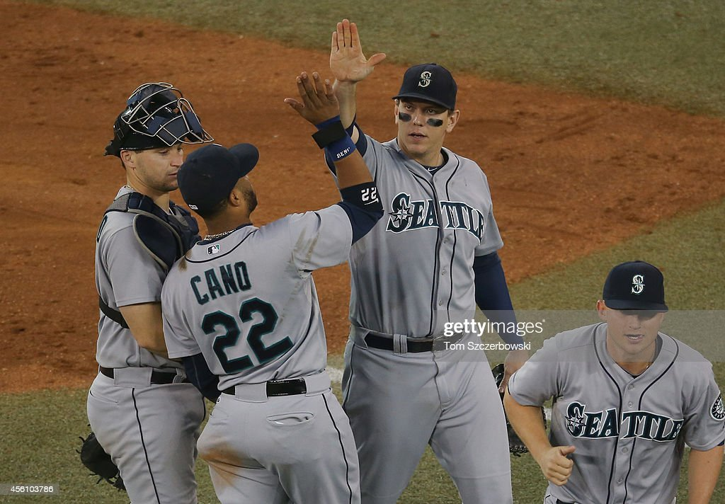 Logan Morrison of the Seattle Mariners celebrates their victory with Robinson Cano during MLB game action against the Toronto Blue Jays on September...