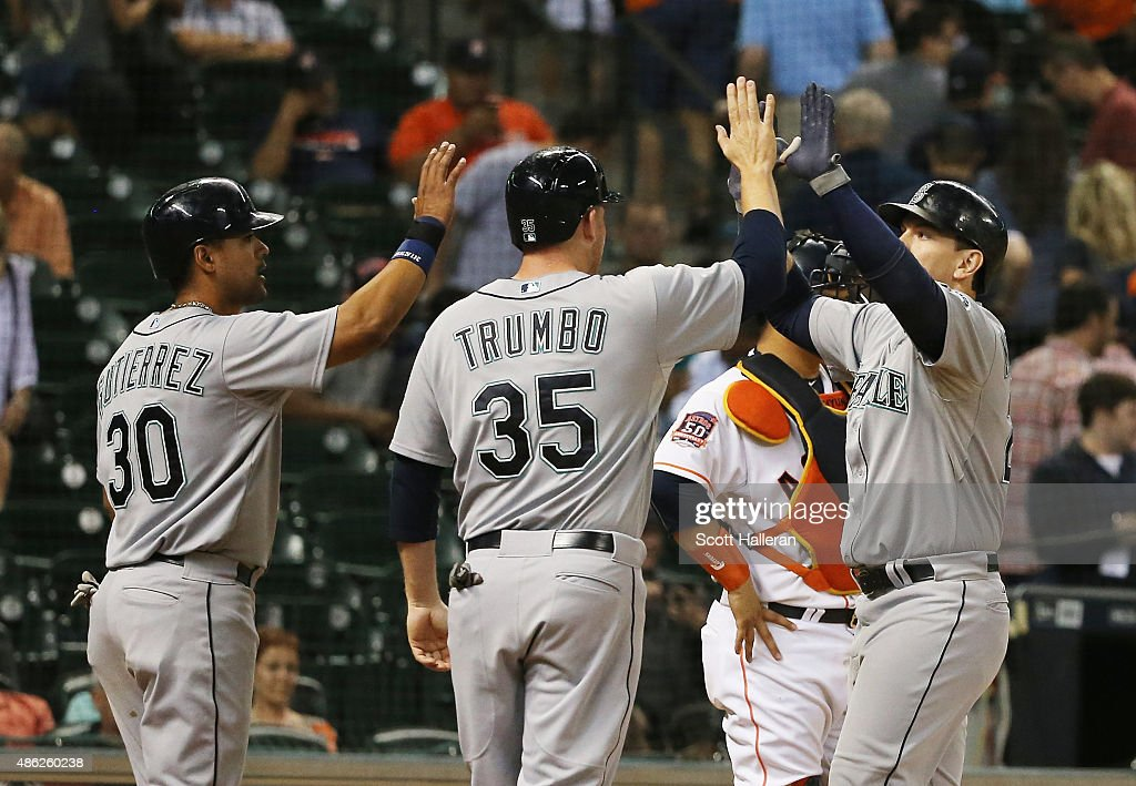 Logan Morrison of the Seattle Mariners is greeted by Franklin Gutierrez and Mark Trumbo of the Seattle Mariners after Morrison hit a threerun home...