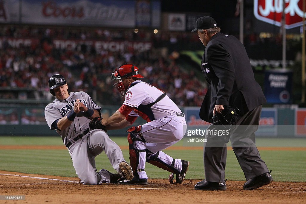 Logan Morrison of the Seattle Mariners is tagged out at home by catcher Chris Iannetta of the Los Angeles Angels of Anaheim as umpire Joe West looks...