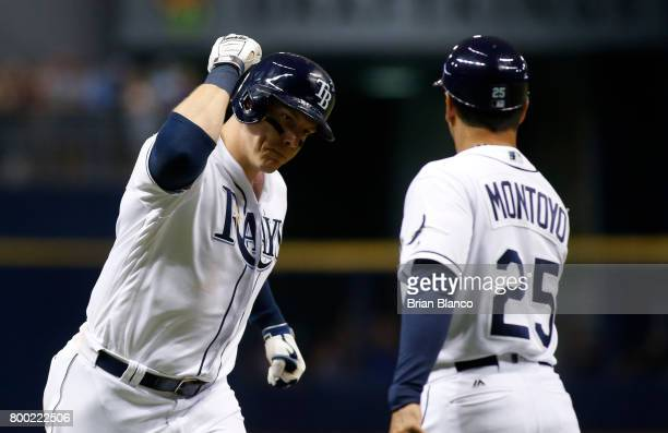 Logan Morrison of the Tampa Bay Rays celebrate with third base coach Charlie Montoyo hitting a home run off of pitcher Miguel Castro of the Baltimore...