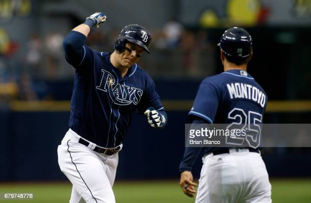 Logan Morrison of the Tampa Bay Rays celebrates with third base coach Charlie Montoyo after hitting a tworun home run during the third inning of a...