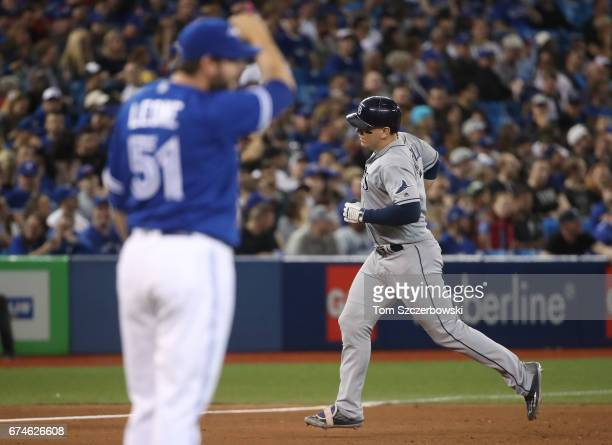 Logan Morrison of the Tampa Bay Rays circles the bases after hitting a tworun home run in the eighth inning during MLB game action as Dominic Leone...