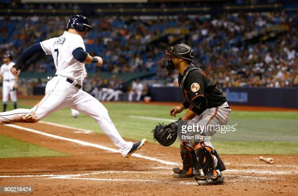 Logan Morrison of the Tampa Bay Rays crosses home plate ahead of catcher Welington Castillo of the Baltimore Orioles to score off of a sacrifice fly...