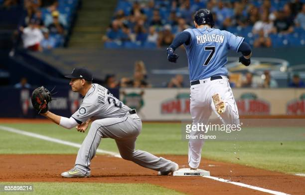 Logan Morrison of the Tampa Bay Rays gets to first base ahead of first baseman Danny Valencia of the Seattle Mariners off of his fielder's choice...
