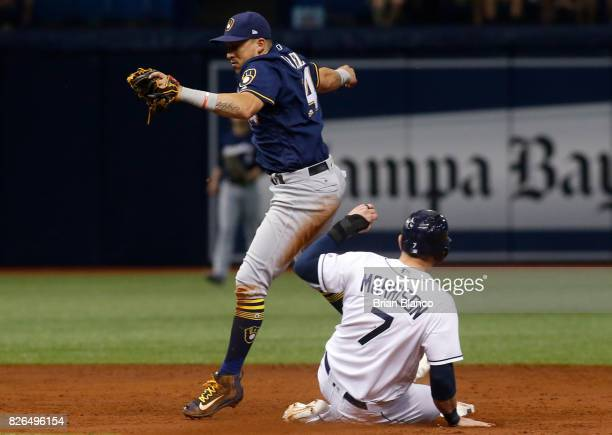 Logan Morrison of the Tampa Bay Rays slides safely into second base as second baseman Hernan Perez of the Milwaukee Brewers attempts to haul in the...