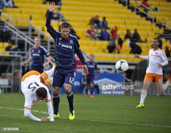 Logan Pause of the Chicago Fire and Cam Weaver of the Houston Dynamo battle for the ball during the first half of their game at Blackbaud Stadium on...