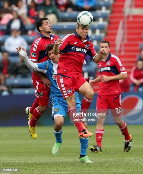 Logan Pause of the Chicago Fire heads the ball in front of Dilly Duka and Michael Farfan of the Philadelphia Union during an MLS match at Toyota Park...